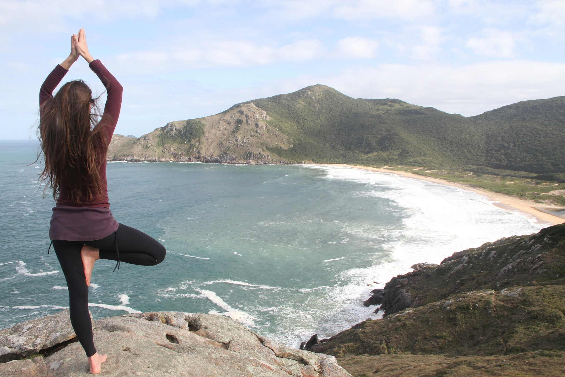 girl doing yoga on mountain cliff overlooking ocean